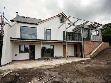 Rear view of full house Rationel window and door installation in Neston, Cheshire. Windows are a dual colour with Grey RAL 7016 externally. All windows and doors are alu-clad timber fitted with triple glazing for added energy efficiency.