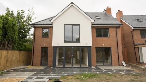 New build development featuring a range of Anthracite Grey (Ral 7016) grey aluminium windows and doors. Here we can see a set of Centor aluminium bifolding doors, and a sliding door from The Knight Collection.