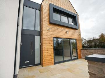 View of entrance featuring RAL7016 grey aluminium door with sandblasted sidelight, bifold doors and aluminium windows.