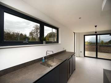 Internal view of aluminium windows and bespoke kitchen.