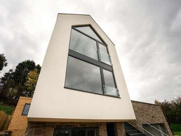 Feature double height aluminium windows with juliet balcony, top window follows the pitch of the roof and internal ceillings.
