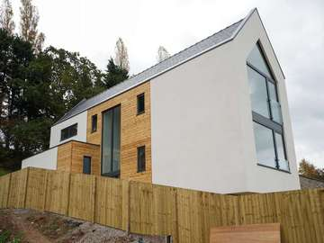 Side view of new build property with timber cladding, k-rend and aluminium curtain walling system.