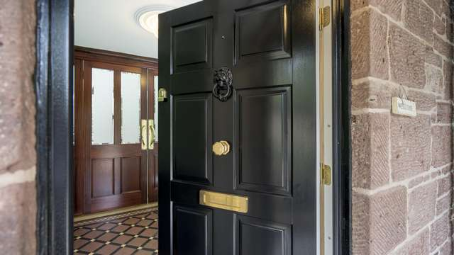 Black timber traditional entrance door with brass door furniture. Custom lion head door knocker in black to match the door colour.
