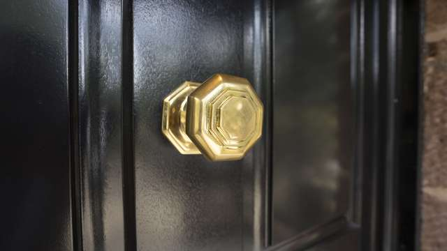 Close up of the brass door pull contrasting well against the black timber door.