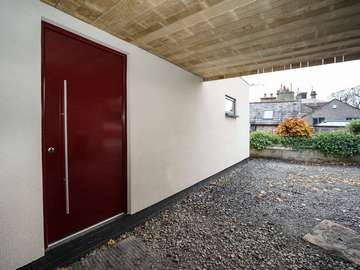Aluminium entrance door finished in powder coated burgundy and stainless steel hardware for a modern look.