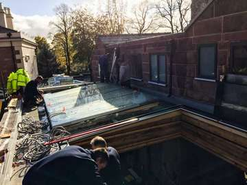 Installation of a large flat roof lantern constructed from glass with glass support for maximum light transfer.