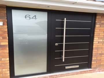 Ormskirk Liverpool. Installtion of our new Aluminium Contempory door range . 44mm and 100mm thick . Sandblst glass to side panel. Double glazed . Argon Gas filled . 1200mm Alpro handles . 9005 Ral.