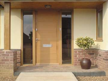 Chester : Installation of a contemporary Kell 1 door design manufactured from oak with natural stain finish . Brushed Stainless letter box and handle