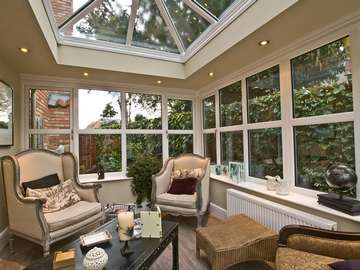 HOYLAKE WIRRAL : Design and build orangery. Quantel ODG white Pvcu roof , glazed with Pilkington Clear Activ double glazed units. Dec 2800 white PvcU Windows with feature ornamental head section