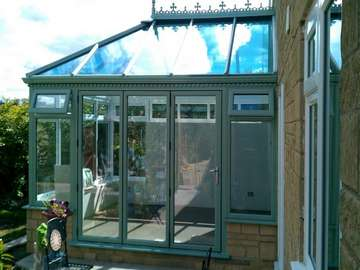 Blackpool : Design and build PvcU Conservatory showing K2 Sage foil roof glazed with Hytherm Self Clean Double glazed units. Matching Sage Green foil PvcU window and Bi fold doors double glazed with Hytherm self cleaning double glazed units.