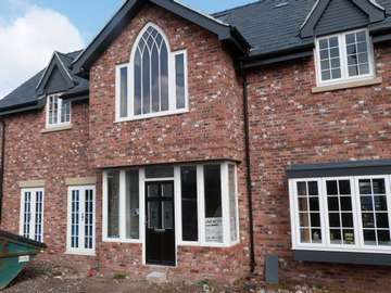 Heswall , Wirral : New Biuld Installtion of Evolution Storm PvcU Windows, also showing an arched Timber frame from G Barnsdales. Front Door by the English door Company